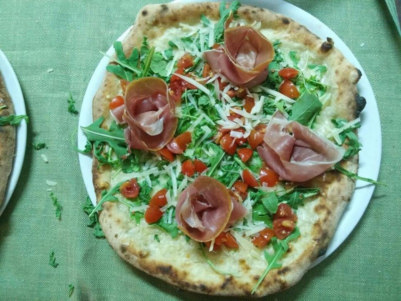 Pizza con pomodorini rucola scaglie e crudo
