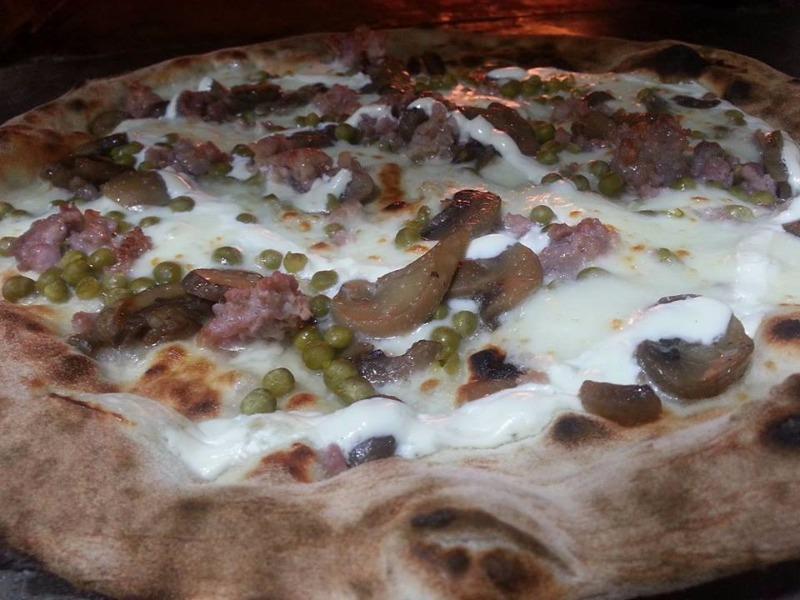Pizza la boscaiola con mozzarella, piselli, panna, funghi di bosco e salsiccia