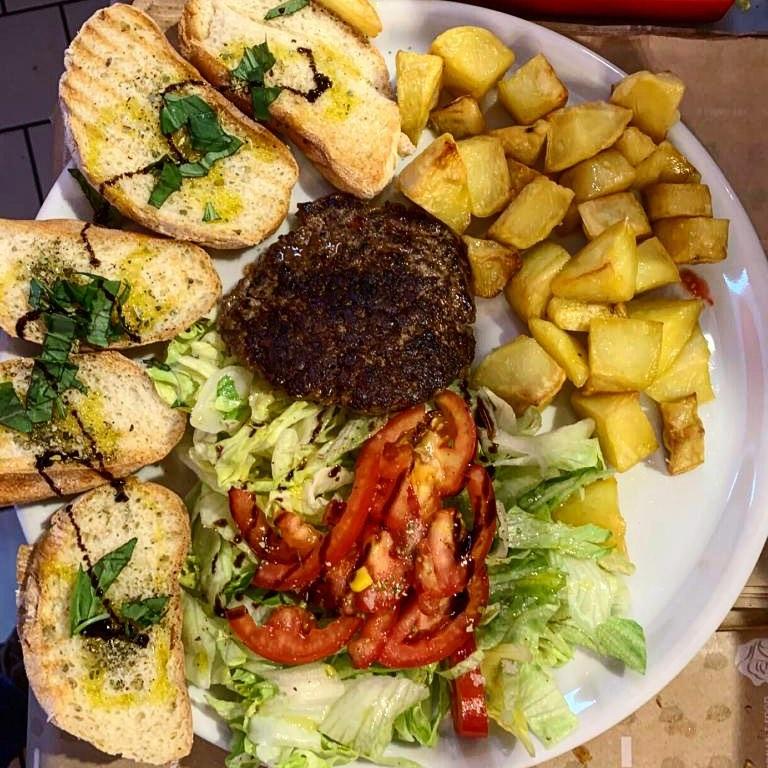 Piatto con: Hamburger, Pomodori, Insalata, Patate al forno, Bruschette condite con basilico, olio e glassa di aceto balsamico