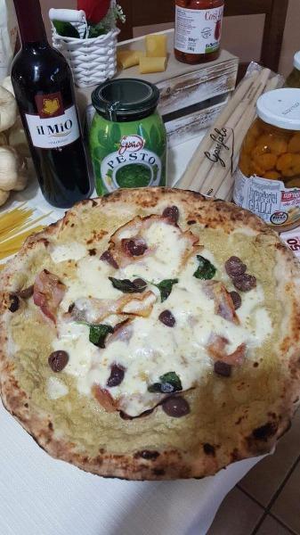 Pizza con  pesto di carciofi, pancetta, olive nere, provolone del monaco