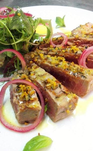 Trancio di tonno rosso profumato agli agrumi con menta, pepe rosa e cipolla rossa marinata.